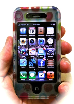 Image of an iPhone 4, it's price having dropped, held in hand